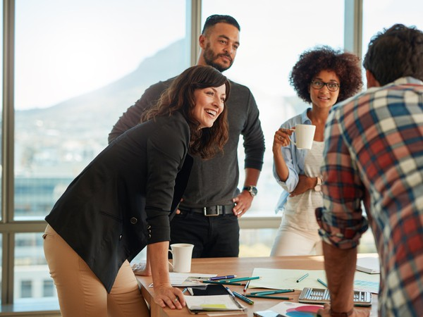 group of young adults around a table full of office supplies_GettyImages-695614764
