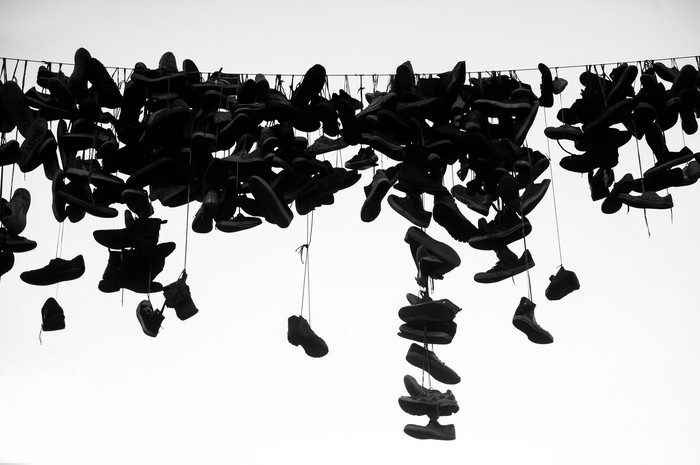 Dozens of shoes hanging from a power line