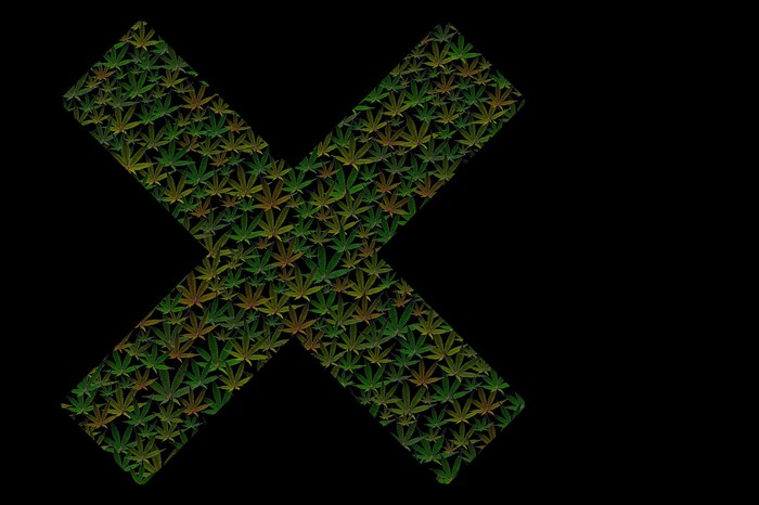Marijuana leaves forming an X against a black background