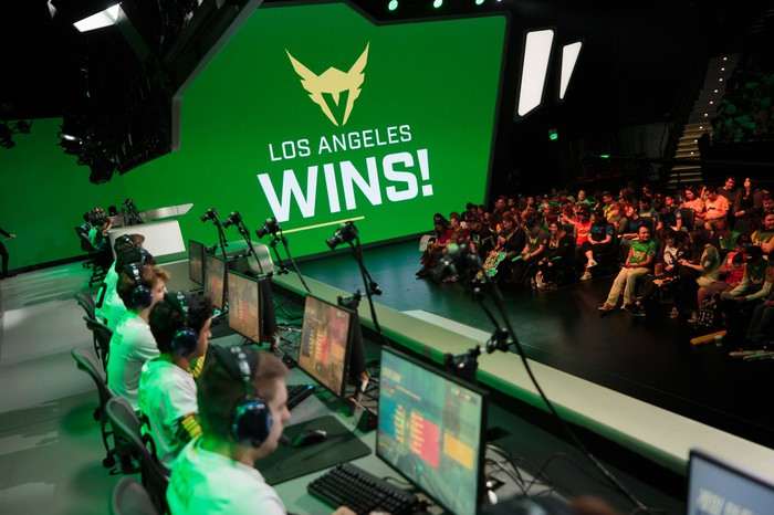 "Members of the Overwatch League team Los Angeles Valiant sitting at computers with a sign reading ""Los Angeles wins!"""