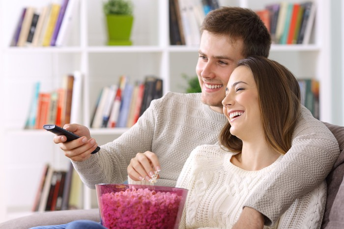 A smiling young couple share a bucket of popcorn on a couch in front of the TV.