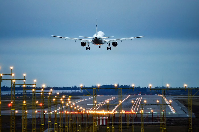 An airplane prepares to land on a runway at twilight.