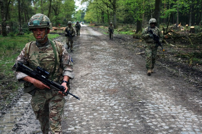 U.S. and British troops on a cobbled road in the woods