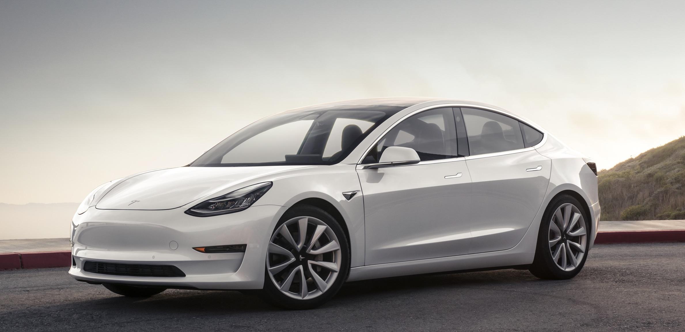 A white Tesla Model 3, a sleek compact luxury sedan
