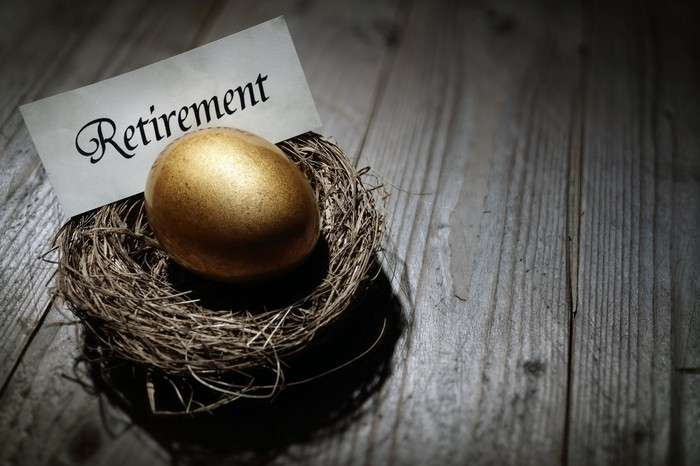"A golden egg resting in a nest with a piece of paper saying ""Retirement."""