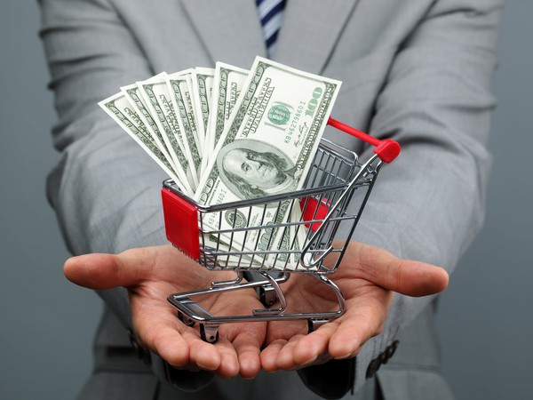 A businessman with shopping cart full of money.
