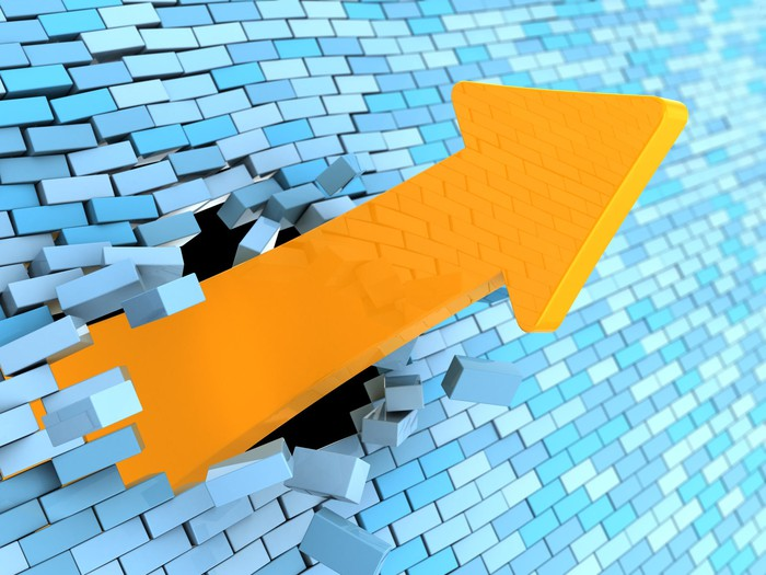 Yellow charting arrow smashing its way upward  through a wall of light-blue bricks.