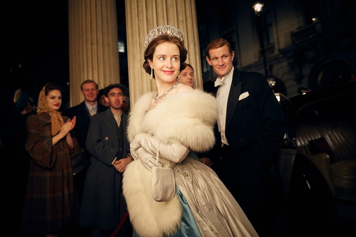 A woman wearing a crown and a man in a tuxedo smiling in a scene from Netflix's The Crown starring Claire Foy and Matt Smith.