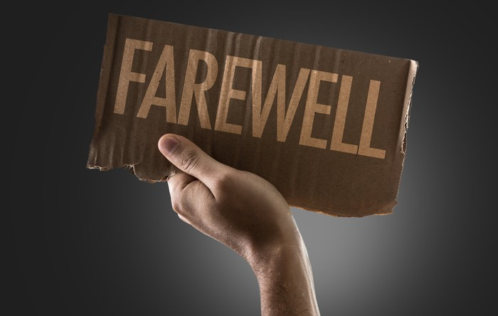 A hand holding up a cardboard sign that reads, Farewell.