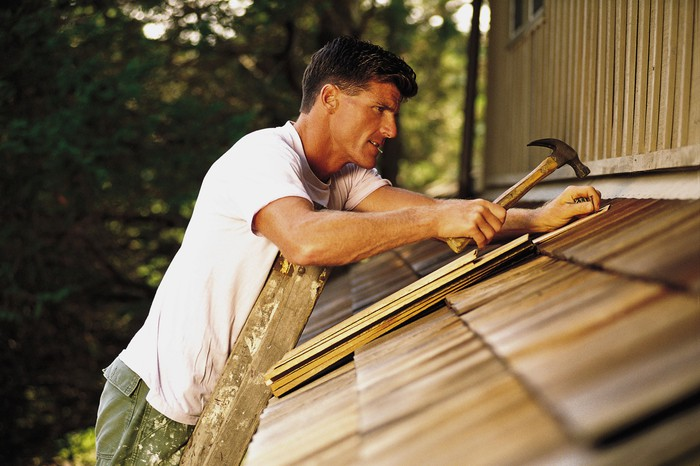 Man hammering in roof shingles