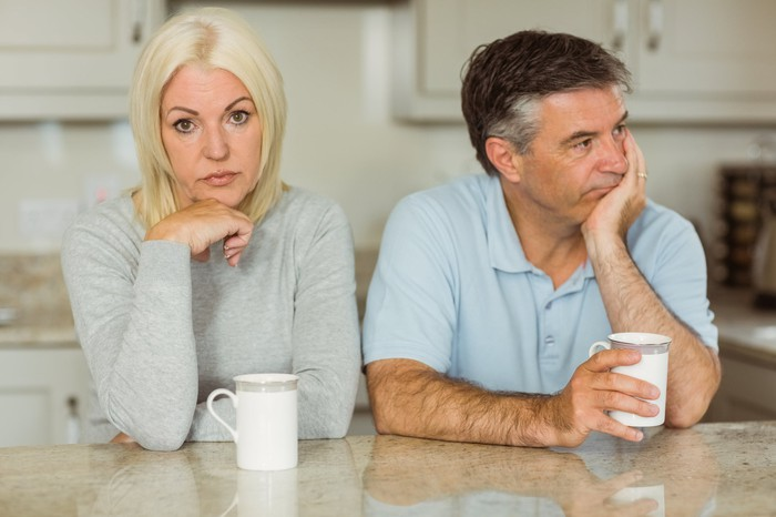 Older man and woman turned away from one another as if annoyed
