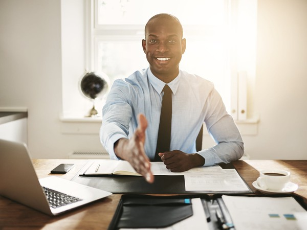 professional man at desk extending a handshake_GettyImages-862298754