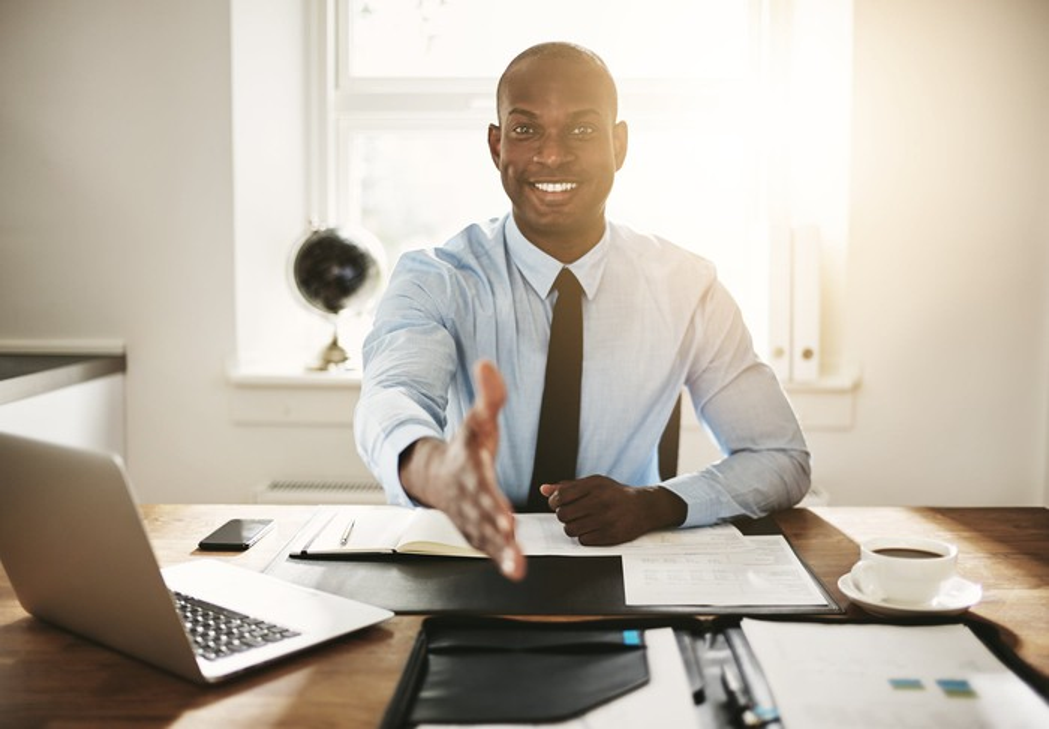 Smiling professional man at desk extending a handshake