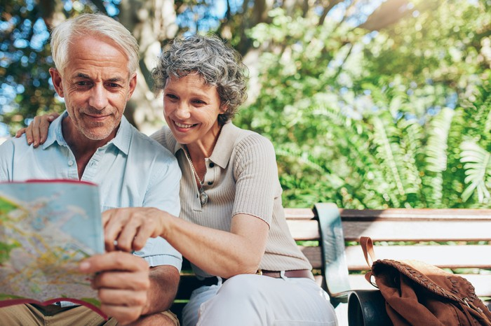 Older couple on a park bench looking at a map