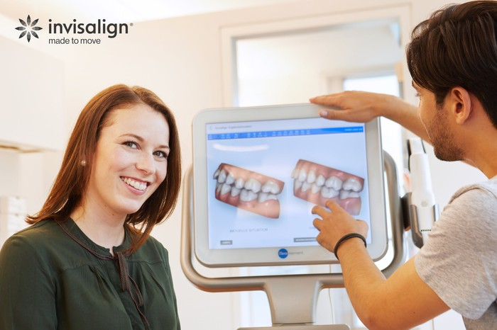 A woman smiling as an orthodontist shows images on a computer screen of before and after images of straightened teeth.
