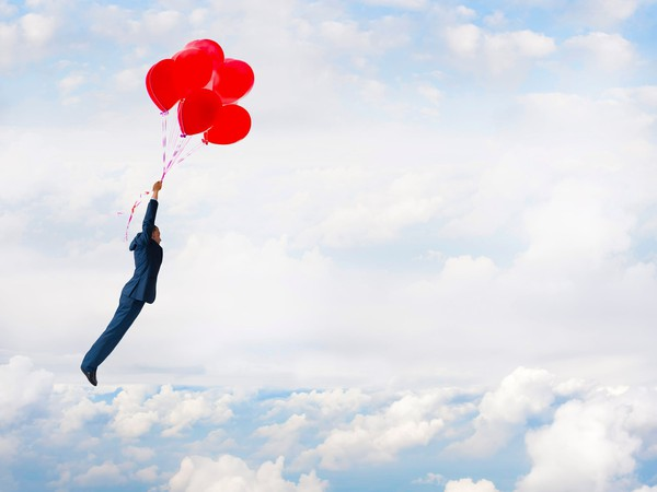 Businessman flying high with red balloons