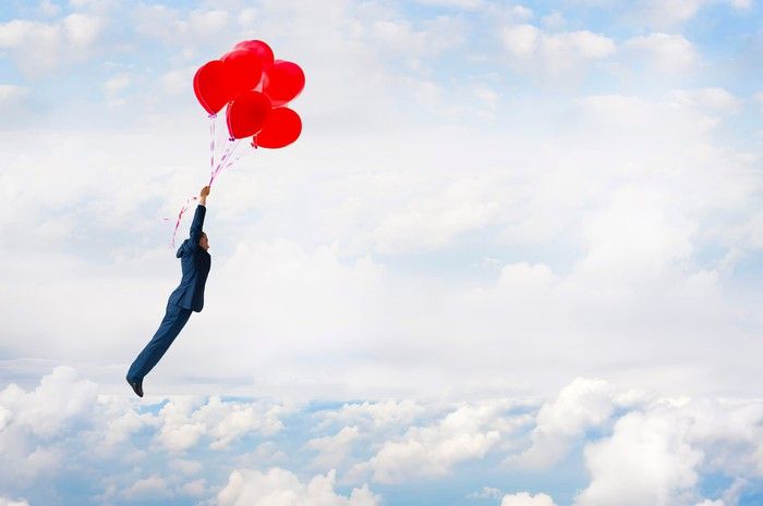 Man in a suit flying above the clouds by holding on to a cluster of red balloons.