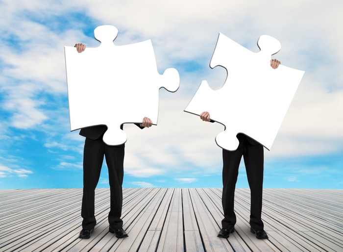 Two men in suits holding up large white puzzle pieces.