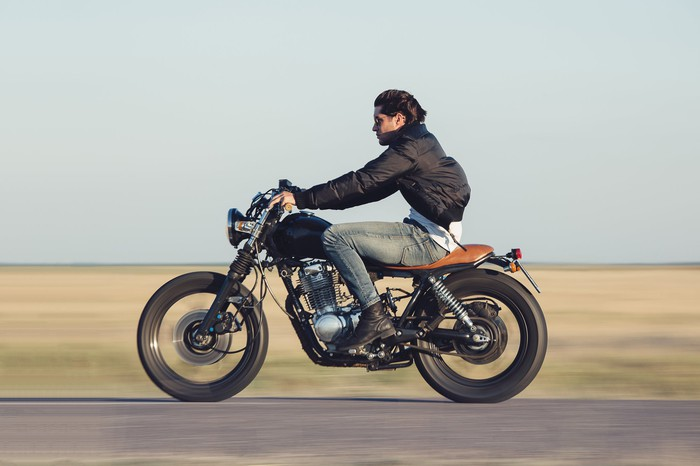 Man riding motorcycle on a rural road.