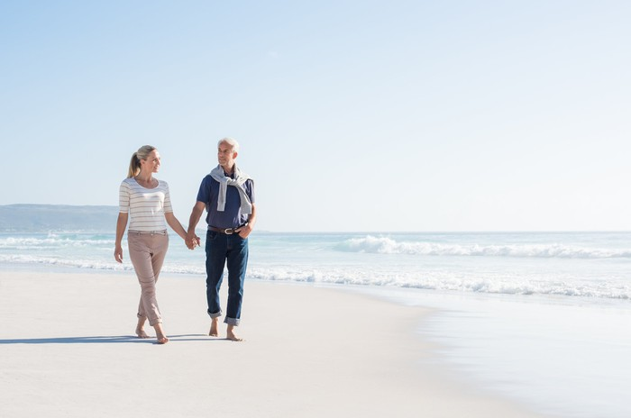 An older couple takes a walk on the beach.