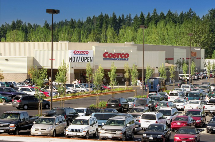"The front of a Costco warehouse with a full parking lot, and a sign reading ""Now open."""