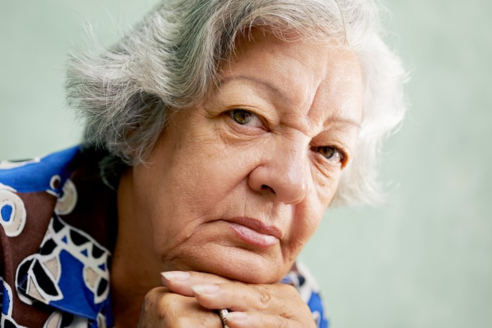 A senior woman in deep thought with her head resting on her interlocked hands.