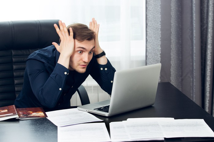 Office worker leaning on his desk, palms pressed to his temples, and staring in horror at his laptop screen.