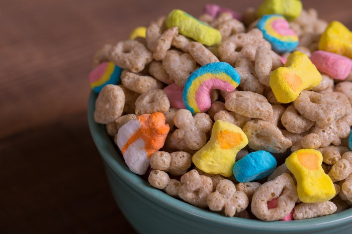 Cereal in a blue bowl on a wood table.