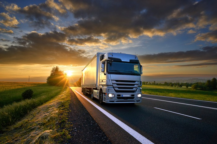 Truck driving on the highway at sunset.