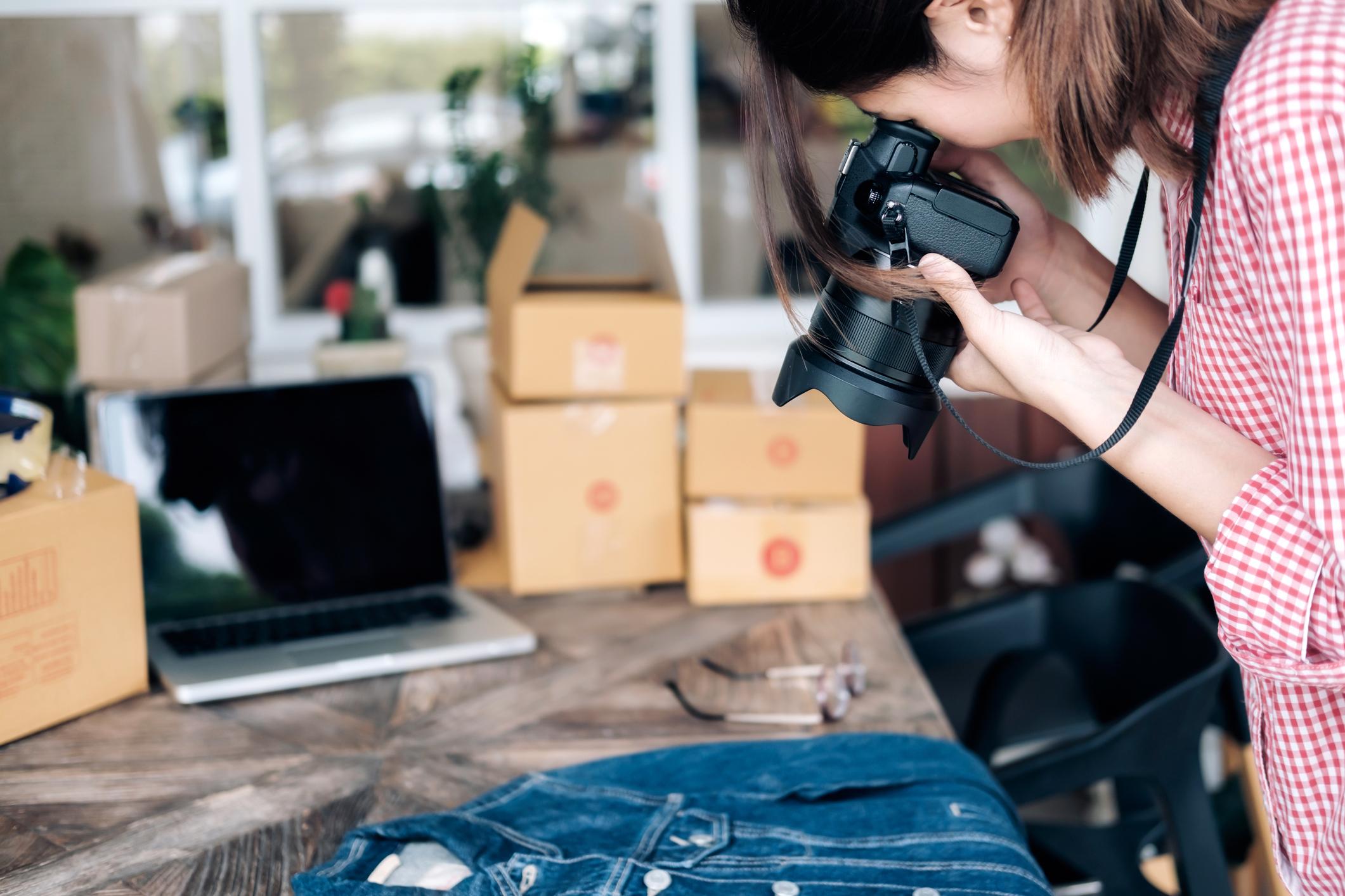 Online seller taking photograph of denim shirt before uploading image to website.