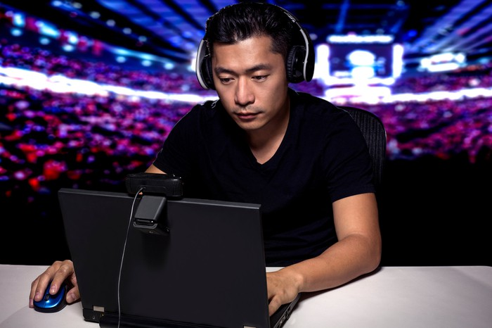 Esports competitive gamer seated in front of laptop in a stadium.