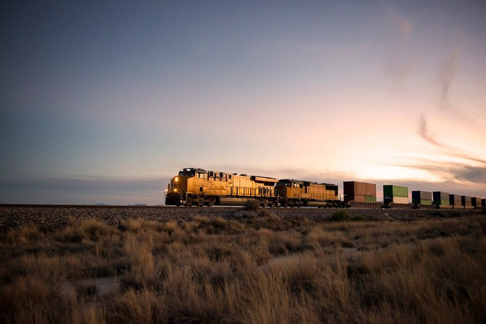 Locomotive pulling a string of train cars across a prairie landscape at dusk.