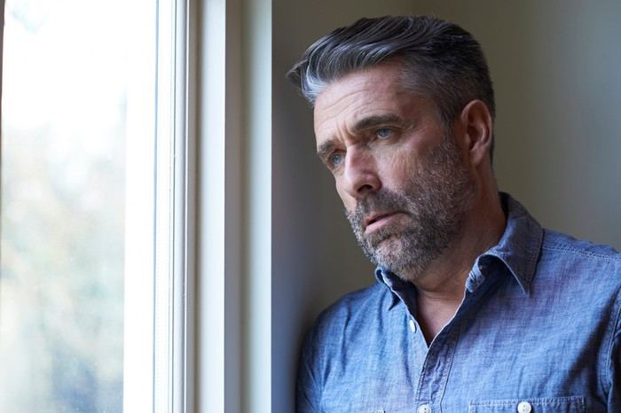 Older man with concerned expression standing next to window