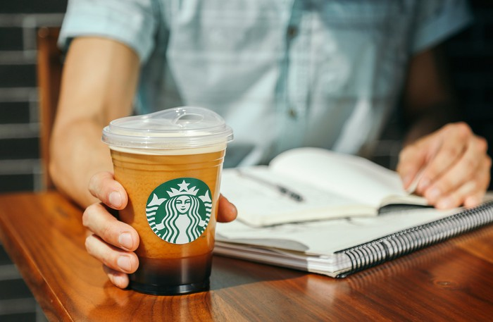 A person reading preparing to pick up a Starbucks coffee drink.