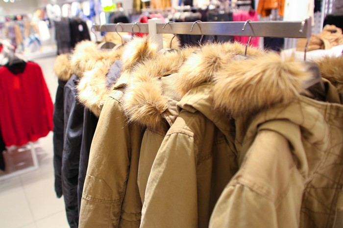 Winter coats on hangers in a store.