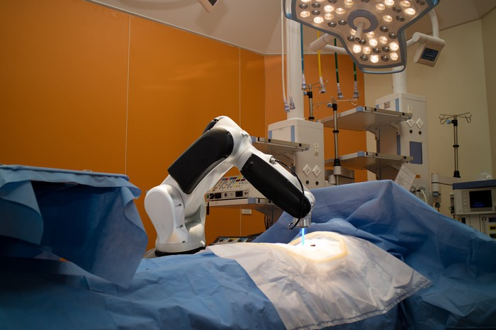 A robotic surgery tool, no unlike the daVinci system, performing surgery on a patient's abdomen.