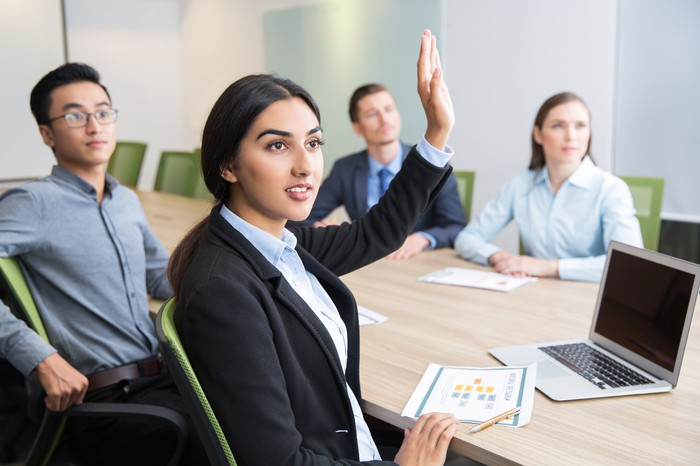 Professionally dressed woman raising her hand during a meeting