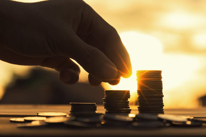 A hand stacking coins in columns against a sunset.