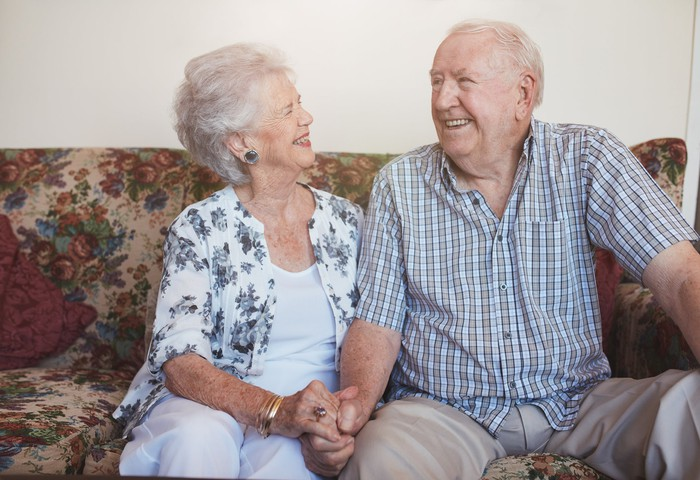 senior man and woman sitting on couch holding hands and smiling