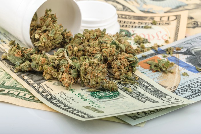 A tipped over white bottle full of dried cannabis lying on a messy pile of cash bills.