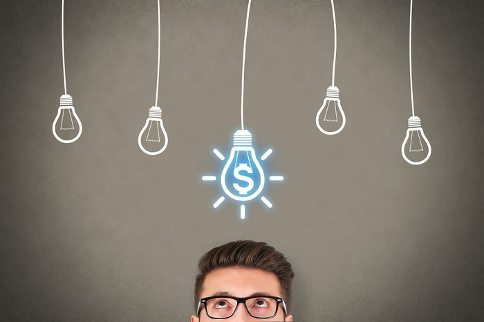 Man with glasses looking up at a chalkboard with five light bulbs drawn on it. The one in the middle has a dollar sign and looks lit up.