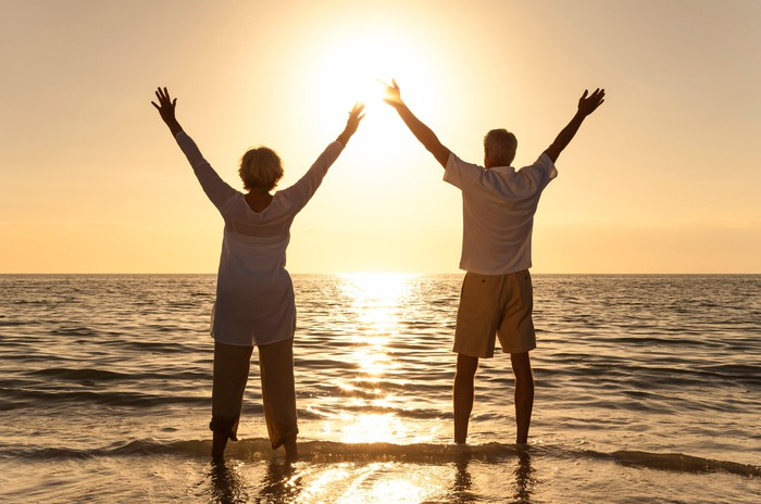 Senior woman and man on a beach at sunset with their arms raised high