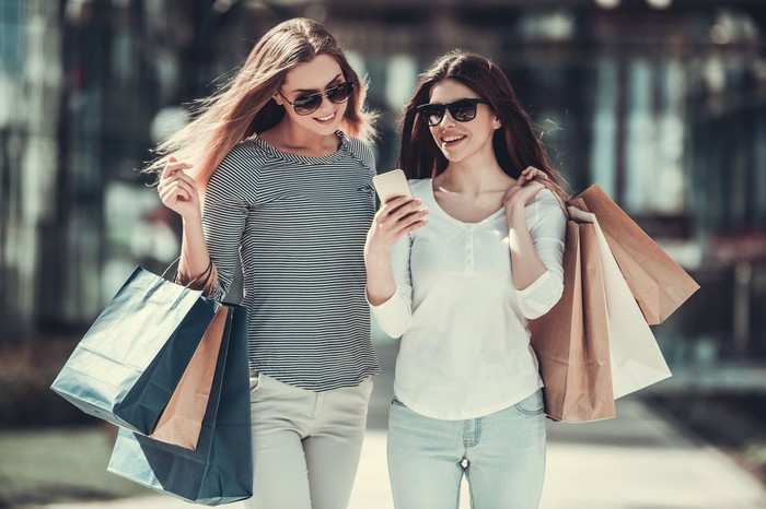 Fashionably dressed women wearing sunglasses and carrying shopping bags while looking at a smartphone.