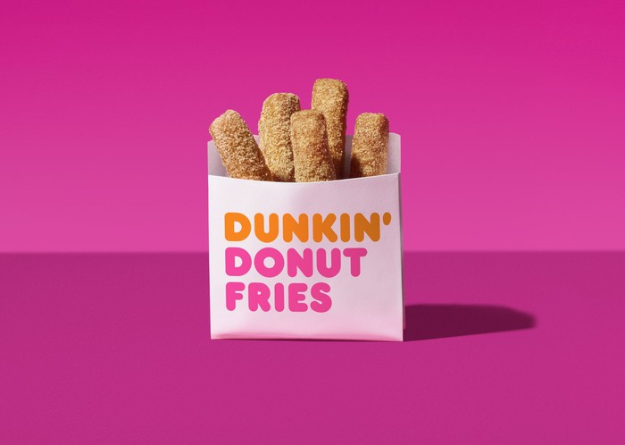 A bag of Dunkin' Donut Fries against a mauve backdrop.