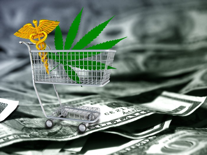 Marijuana leaf and caduceus in shopping cart on top of U.S. cash