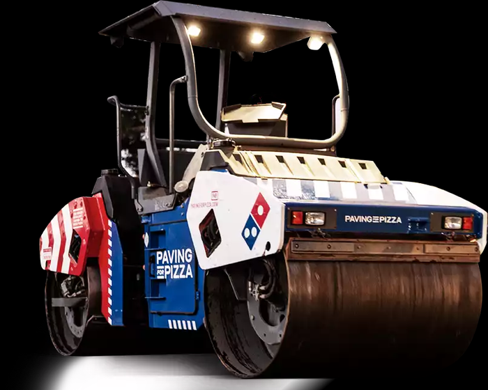 A steam roller painted in red white and blue with the Domino's Pizza logo on it.
