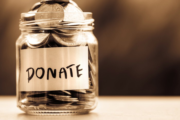 "A glass jar labeled ""donate"" full of coins."