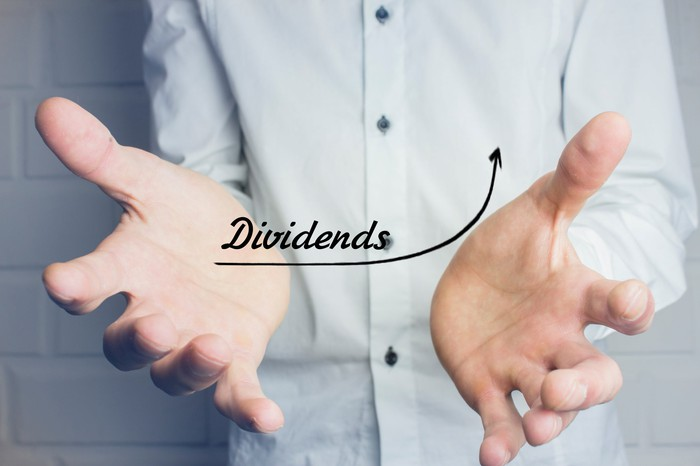 """The word """"dividends"""" on a rising chart between a man's hands."""