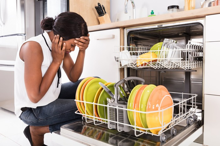 A woman with hands to head squats in front of a dishwasher loaded with dishes.