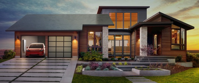 A Tesla Model 3 parked in the garage of a house with a Powerwall and Tesla solar roof
